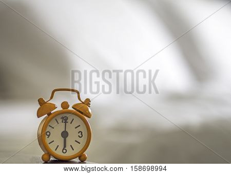Alarm clock on bed in morning with sun light background bed