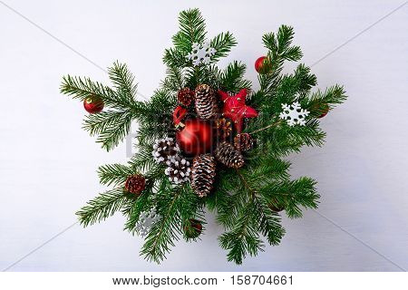 Christmas red ornaments and snowy decorated pinecone wreath. Christmas background with fir branches.