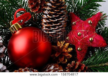 Christmas red ornaments and snowy decorated pinecone. Christmas background with fir branches.