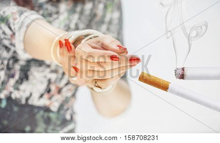 Female's hands with red nails taking a cigarette