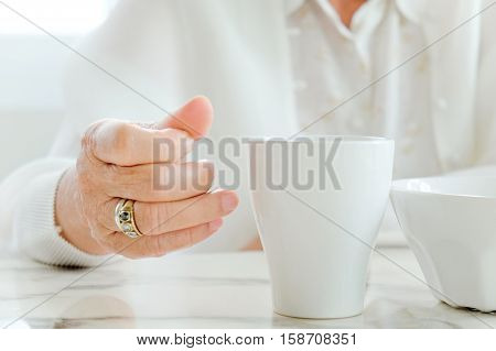 Close up image of senior women with drink, meal time