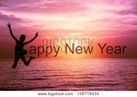 Happy new year card 2017. Silhouette of happy girl in swimwear jumping on tropical sea with sunset sky background. Kid jumping as part of the word Happy New Year with ocean and sunrise background.