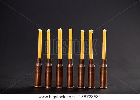 Candles and empty rifle cartridges. As a symbol of war and victims. Located on black cardboard as a background.