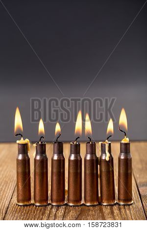Burning candles and empty rifle cartridges. As a symbol of war and victims. Located on brown wooden table against black background.
