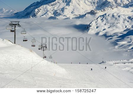 Alpine winter mountain landscape with ski lift and slopes. French Alps covered with snow in sunny day. Val-d'Isere, Alps, France