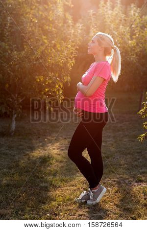 Pregnant woman enjoying sunrise at garden, side view. Expectant female holding her belly while relaxing outdoor. Unity with nature, calm, peacefulness , healthy lifestyle concept
