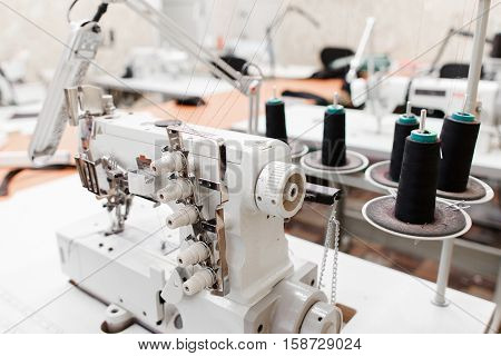 Professional overlock sewing machine with black thread in workshop. Equipment for edging, hemming or seaming clothes at tailors shop.