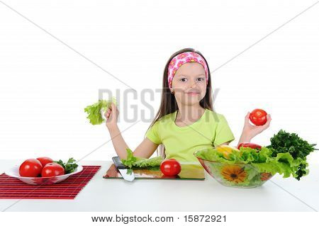 Little girl cut tomatoes at the table