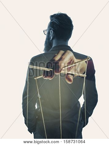 Image created using multiple exposures. Image of a hand that manipulates of a man in a business suit.