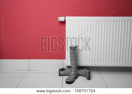 Gumboots near heating radiator on pink background