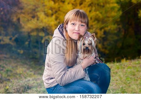 Young woman holding yorkshire terrier on her hands