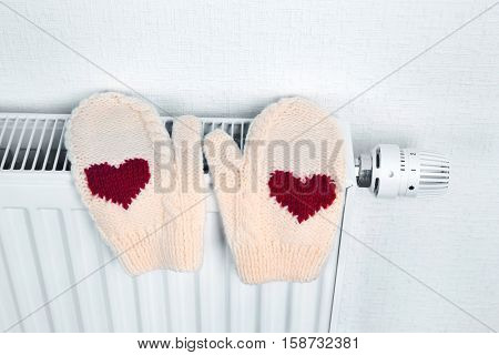 Heating radiator with knitted mittens indoors