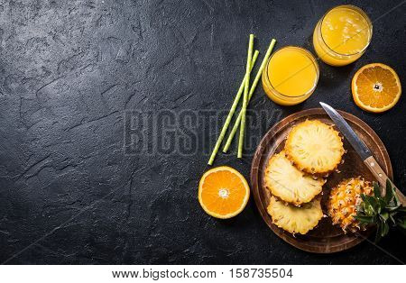 Fresh pineapple juice in the glass with pineapple fruit on black background, top view with copy space