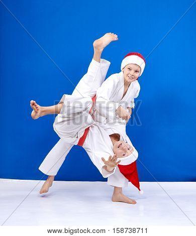 Throws of judo are training boys in caps of Santa Claus