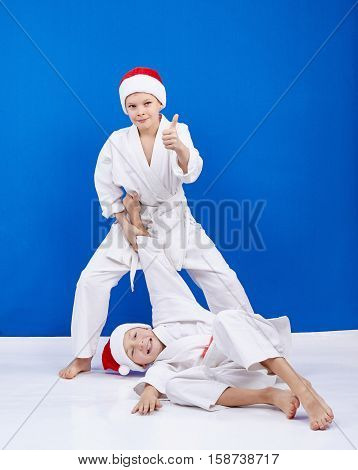 Two boys are trained judo throws in Santa Claus caps
