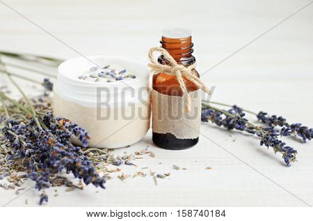 Lavender plant-based beauty care products line. Facial cream in jar, essential oil bottle, craft paper label, dried purple flowers twigs.