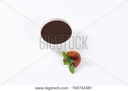 bowl of date syrup with dates on white background