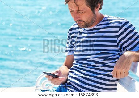 Man in striped sailor shirt using mobile phone at seaside beach to send a SMS message defocus sea surface in the background