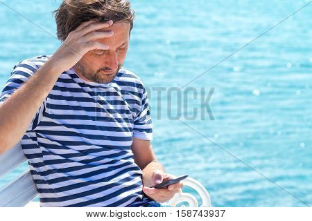 Worried man in striped sailor shirt reading mobile SMS message at seaside beach defocus sea surface in the background