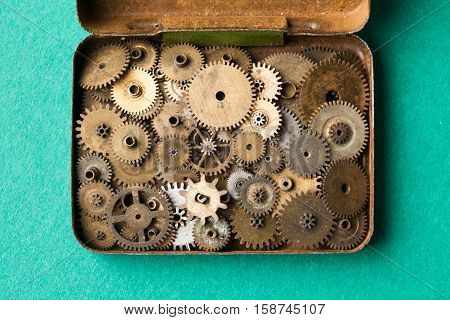 Steampunk gears collection in opened vintage box. macro view, green paper background. Shallow depth of field, soft focus.