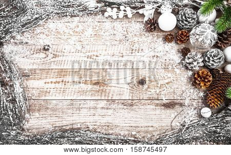 Christmas festive background with pinecone balls. Holiday greeting card branch old wooden board rustic style. Copyspace and top view