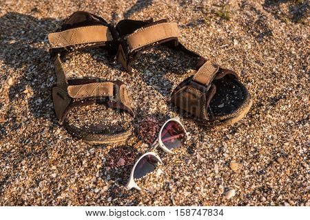 Sandals and sunglasses. Sand with crushed seashells. Bright sun of the tropics. Escape from noise and problems.