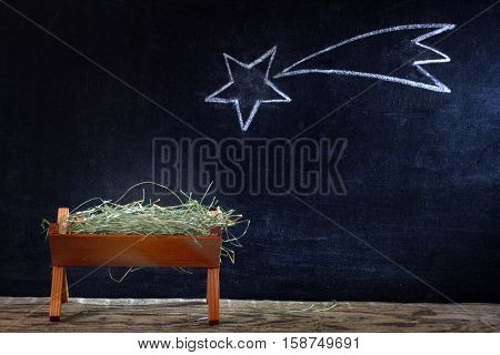Birth of Jesus with manger and star on blackboard abstract christmas nativity scene