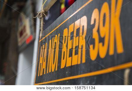 Hanoi, Vietnam - Nov 26, 2016: Advertising sign of Hanoi beer, the popular drink in Hanoi, hang outside of a side walk restaurant at Hanoi old quarter street area.