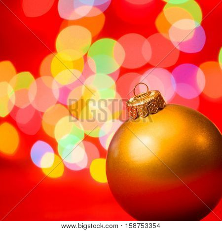 Golden christmas bauble with blurred lights in background