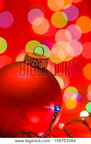 Red christmas bauble with blurred lights in background
