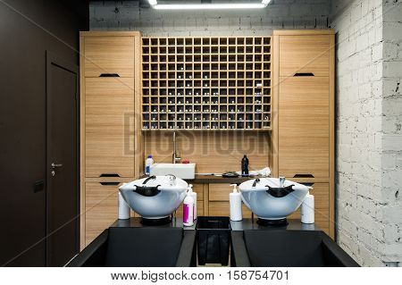 Beauty salon interior - a row of hair washing sinks - white washbasins for hairdresser
