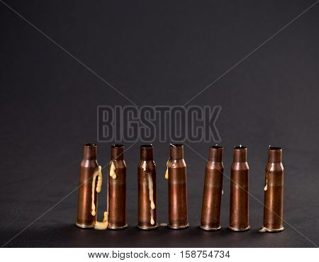 Empty rifle cartridges with melted candles. As a symbol of war and victims. Located on black cardboard as a background.