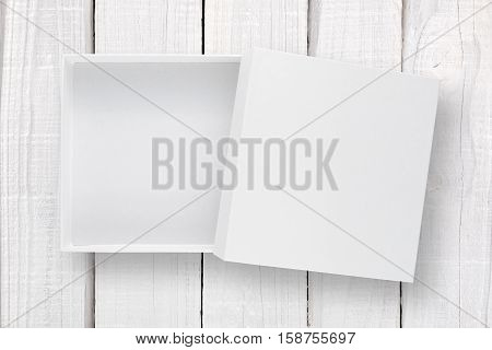 White box with cover on white wooden background