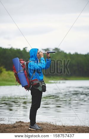 Side view of hiker looking through spyglass