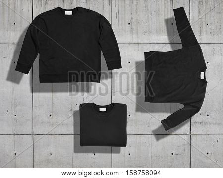 Unlabeled black short women cotton sweatshirt shot in three different shapes on concrete background