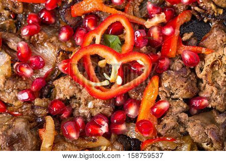 Stewed chicken livers with paprika and pomegranate seeds. Macro. Photo can be used as a whole background.
