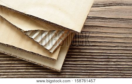 Corrugated cardboard sheets on rough wooden background. Ripped sheet.