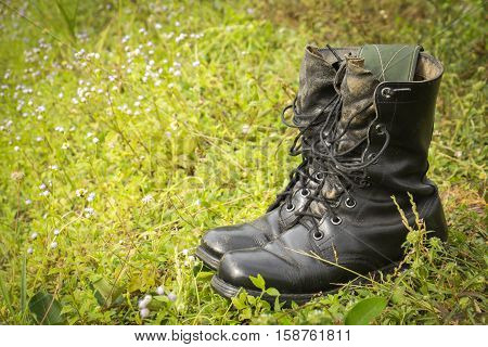the old black combat boots on grass.
