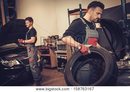 Professional car  mechanic replace tire on wheel in auto repair service.