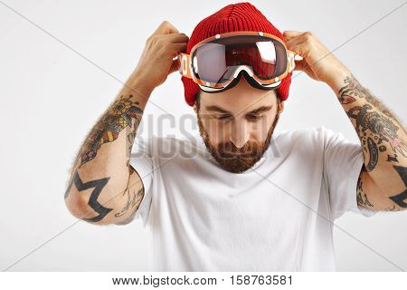 Close up shot of a hipster in a red beanie and shite unlabeled shortsleeve t-shirt putting on his snowboard goggles isolated on white