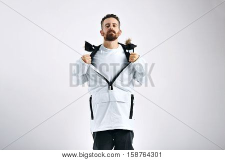 Attractive young snowboarder showing unlabeled white t-shirt under his white snowboarding anorak against white wall background