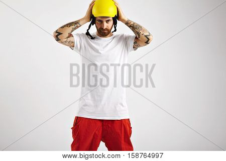 Portrait of a slightly smiling attractive young snowboarder in red pants and blank white cotton t-shirt putting on his unlabeled yellow helmet against white wall background