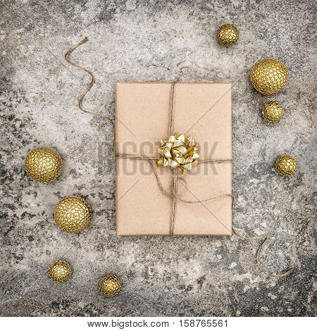 Wrapped gift and christmas decoration on concrete stone background. Perfect for social media square picture