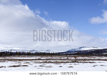 Spring in the mountains. Snow, clouds and sunshine. Partly snow and partly wetland.