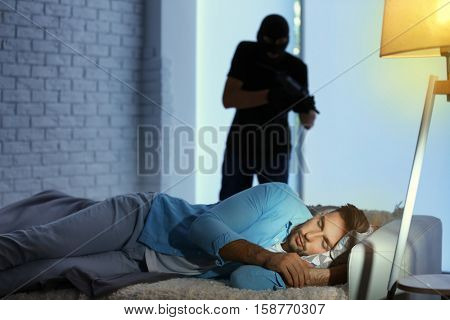 Thief with gun and scared man on bed