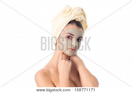 attractive girl takes care her skin with cleansing mask on face and towel on head isolated on white background. Health care concept. Body care concept. Young woman with healthy skin.