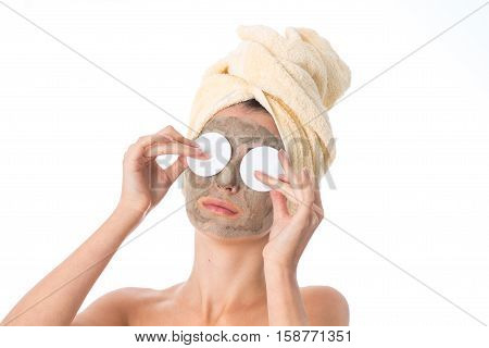Young pretty girl takes care her skin with cleansing mask on face and towel on head isolated on white background. Health care concept. Body care concept. Young woman with healthy skin.