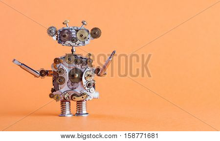 Steampunk style robot handyman with screwdriver. Funny toy mechanical character repair service concept. Aged gears cog wheel hand clock parts. Shabby grunge texture. Orange background copyspace