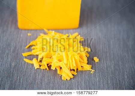 Grated  yellow cheese on a grey background