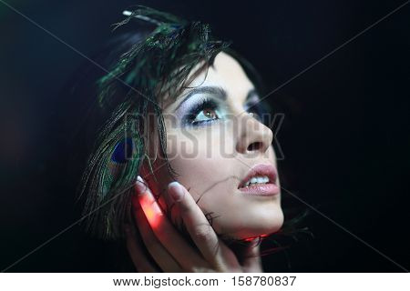 Portrait of a beautiful girl with feather